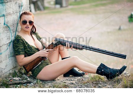 Sexy military woman model with weapon outdoors poster