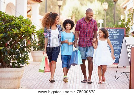 Family Walking Along Street With Shopping Bags