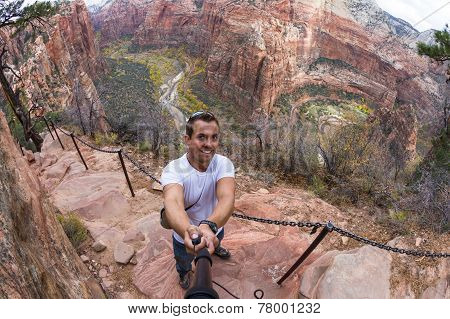 young caucasian man taking a selfie over the steep cliffs of the Angels Landing hiking trail in Zion NP poster
