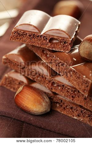 Tasty porous chocolate with nuts, on wooden table poster