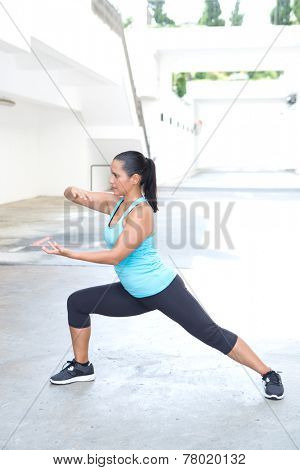 Beautiful hispanic sport woman demonstrating tai chi stance  'shuttle back and forth', outdoor. Concept of healthy lifestyle.