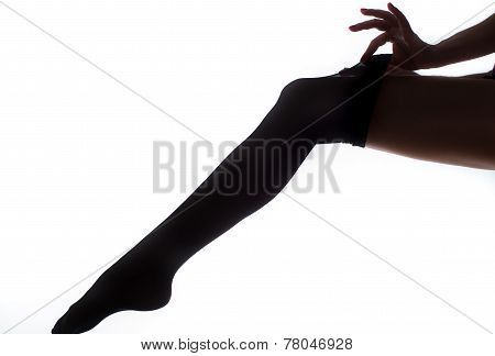 lady puts on stockings in silhouette