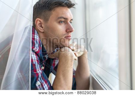 Handsome pensive man guy watching through the window concept sadness sorrow pain waiting
