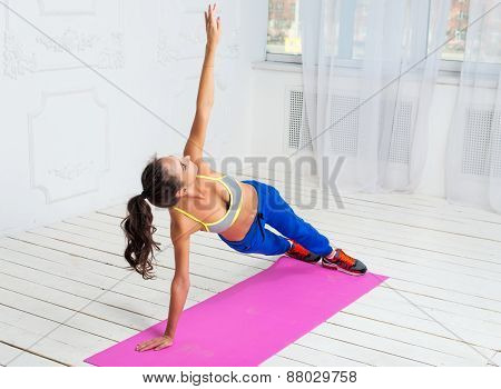Active sportive woman doing handstand exercise practicing the side plank pose during yoga class in a