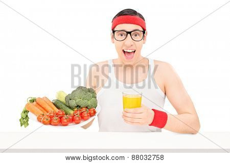 Nerdy young guy holding a glass of orange juice and a plate full of fresh vegetables seated on a table isolated on white background