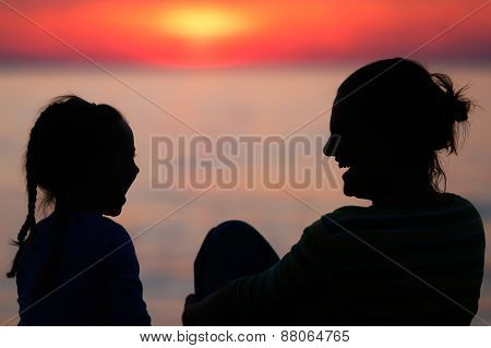 Mother And Daughter Laughing At Sunset
