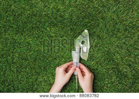 Hands holding inhaler mask over green grass.