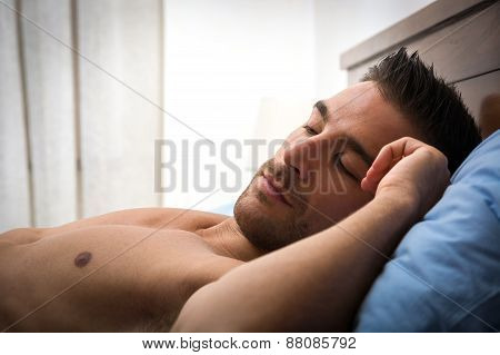 Handsome shirtless athletic young man sleeping in bed