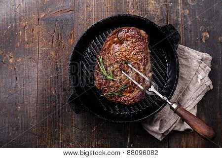 Grilled Black Angus Steak And Meat Fork On Grill Iron Pan On Wooden Background
