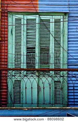 Green Wood Venetian Blind And A Red Blue Wall