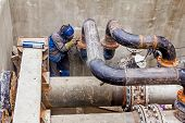 Welder is welding pipe junction completing a manhole for heating pipeline system poster