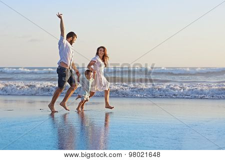 Positive Family Running Along Sea Edge On The Beach