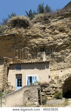 House Facade In Front Of A Cave In The Mountain In The Old Village Of Cadenet, South France