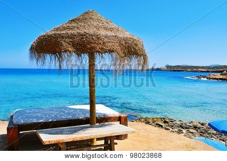 detail of a relaxing area in a Cala Conta beach in Ibiza Island, Spain, with a comfortable sunlounger and a rustic umbrella made of natural fibers