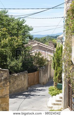 Narrow street with typical houses plants and current lines under the blue sky in the old mountain village of Cadenet Provence France region Luberon poster