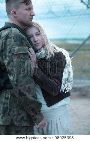 Sad woman hugging military husband and saying goodbye poster