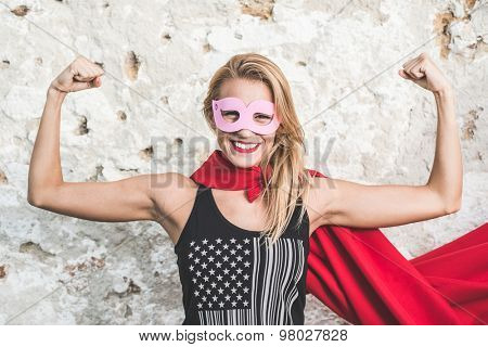 Young woman posing as superhero or superwoman