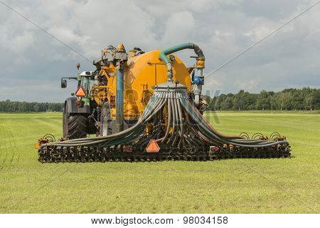 Injecting Of Liquid Manure With Tractor And Yellow Vulture Spreader Trailer