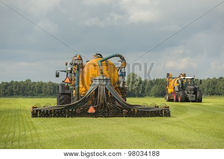 Injecting Of Liquid Manure With Two Tractors And Yellow Vulture Spreader Trailers.
