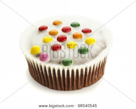 Cupcake with white chocolate icing and smarties isolated on white background