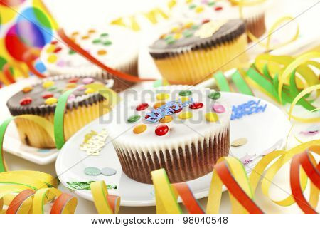 cupcakes with chocolate icing and smarties, surrounded by birthday party decoration