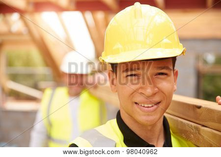 Portrait Of Builder And Apprentice Carrying Wood On Site