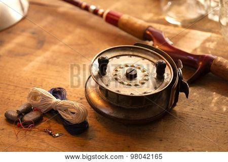 Vintage fishing reel, and rod on old wooden table. Warm lighting.