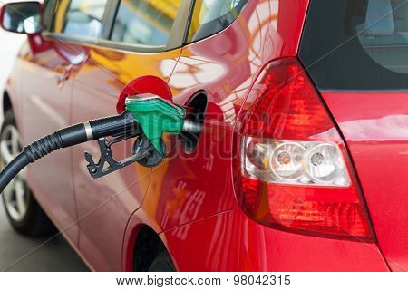 Red car at gas station being filled with fuel
