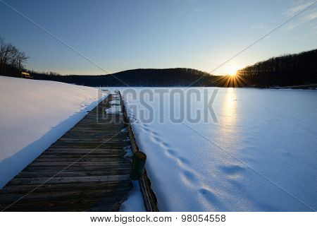 Dock and Frozen Lake at Sunset