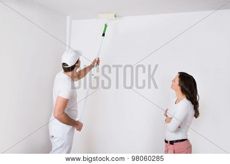 Woman Looking At Painter Painting On Wall