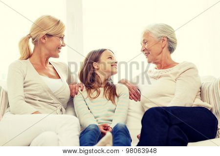 family, happiness, generation and people concept - smiling mother, daughter and grandmother sitting on couch at home poster