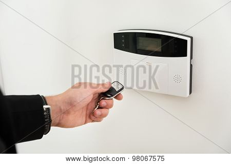 Hands With Remote Control In Front Of Security System
