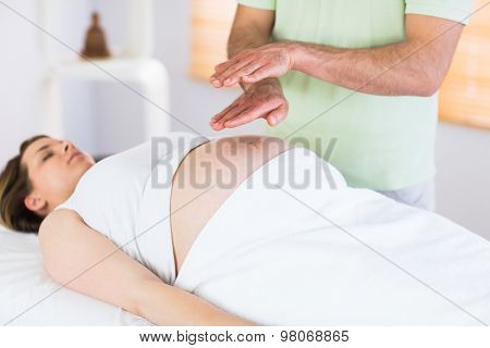 Relaxed pregnant woman getting reiki treatment in a studio