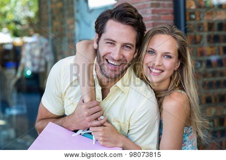 Portrait of smiling couple with shopping bags embracing at shopping mall