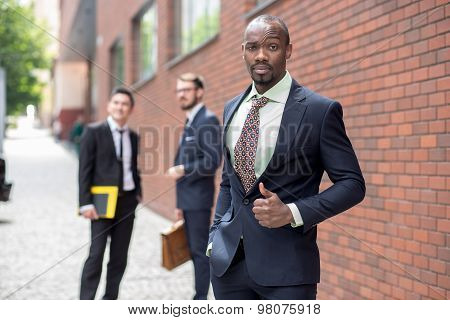 Portrait of multi ethnic business team.Three men standing against the background of red brick wall. The one doubtful man is  African-American. Other men is Chinese and European. the concept of doubt in the success of the transaction poster
