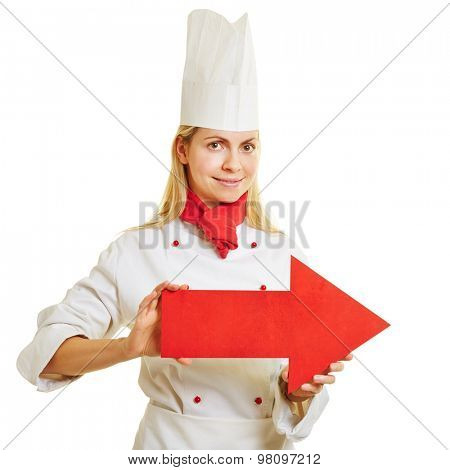 Smiling female cook in apprenticeship holding a big red arrow to the right
