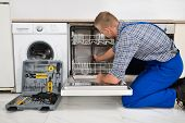 Young Man In Overall With Toolbox Repairing Dishwasher poster