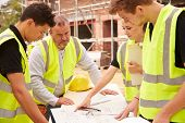 Builder On Building Site Discussing Work With Apprentice poster