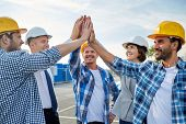 business, building, partnership, gesture and people concept - close up of smiling builders and architects in hardhats making high five outdoors poster