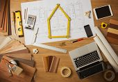 Architect and home interior decorator desktop with tools laptop wood swatches and home project draft top view a meter is composing a house at center poster