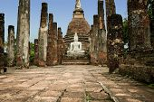 ancient seated buddha staue in the temple ruins of sukhothai in thailand poster