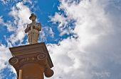 A marble soldier stands eternal guard atop the column of a rural war memorial in Australia. He stands agains a blue sky that holds the promise of rain in the gathering storm clouds poster