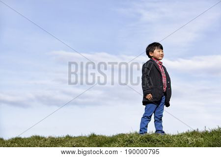 Chinese boy standing in grass