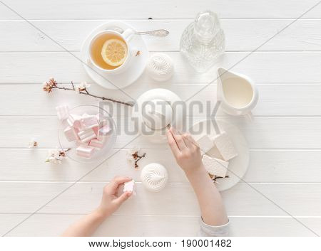 tiny hands holding sweets for tea ceremony in pastel pink and white colors, porcelain, topview