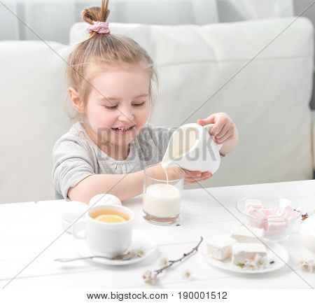 Little girl pouring milk into her teacup, sweets around her, ready for her teatime