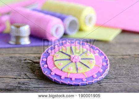 Abstract flower made of colorful felt and light pink beads. Handmade beautiful flower, thread, colorful felt sheets, thimble on old wooden table. Easy, fun and quick children hand sewing concept