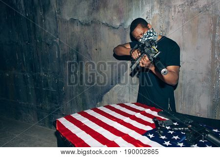 Black soldier checks his weapon. Mercenary man with rifle in hand on dark gray background. Outlaw, ghetto, patriotic war, armed attack concept