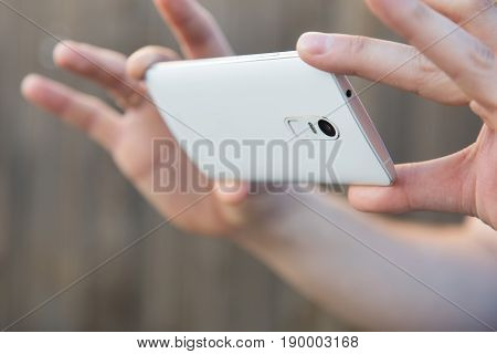 A Man Takes Pictures Or Shoots Video On A Smartphone. Close-up Of Hand And Gadget In A Horizontal Po