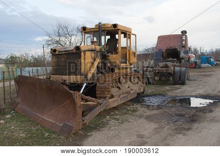 Old abandoned yellow bulldozer. Old rusty and weathered bulldozers