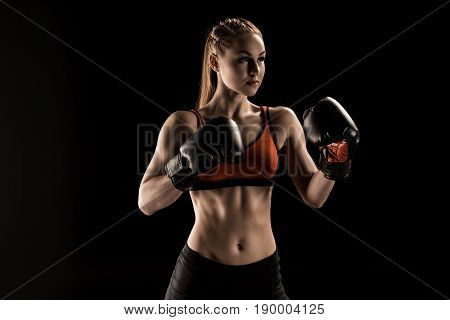 Muscular Young Sportswoman In Boxing Gloves Training And Looking Away